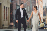 bride and groom smile and walk holding hands down cobblestone street in downtown Buffalo, NY on their wedding day