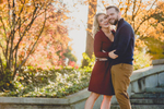 couple smiles for photographer during weddding engagment portrait photography session on steps to Hoyt Lake in Delaware Park in Buffalo, NY