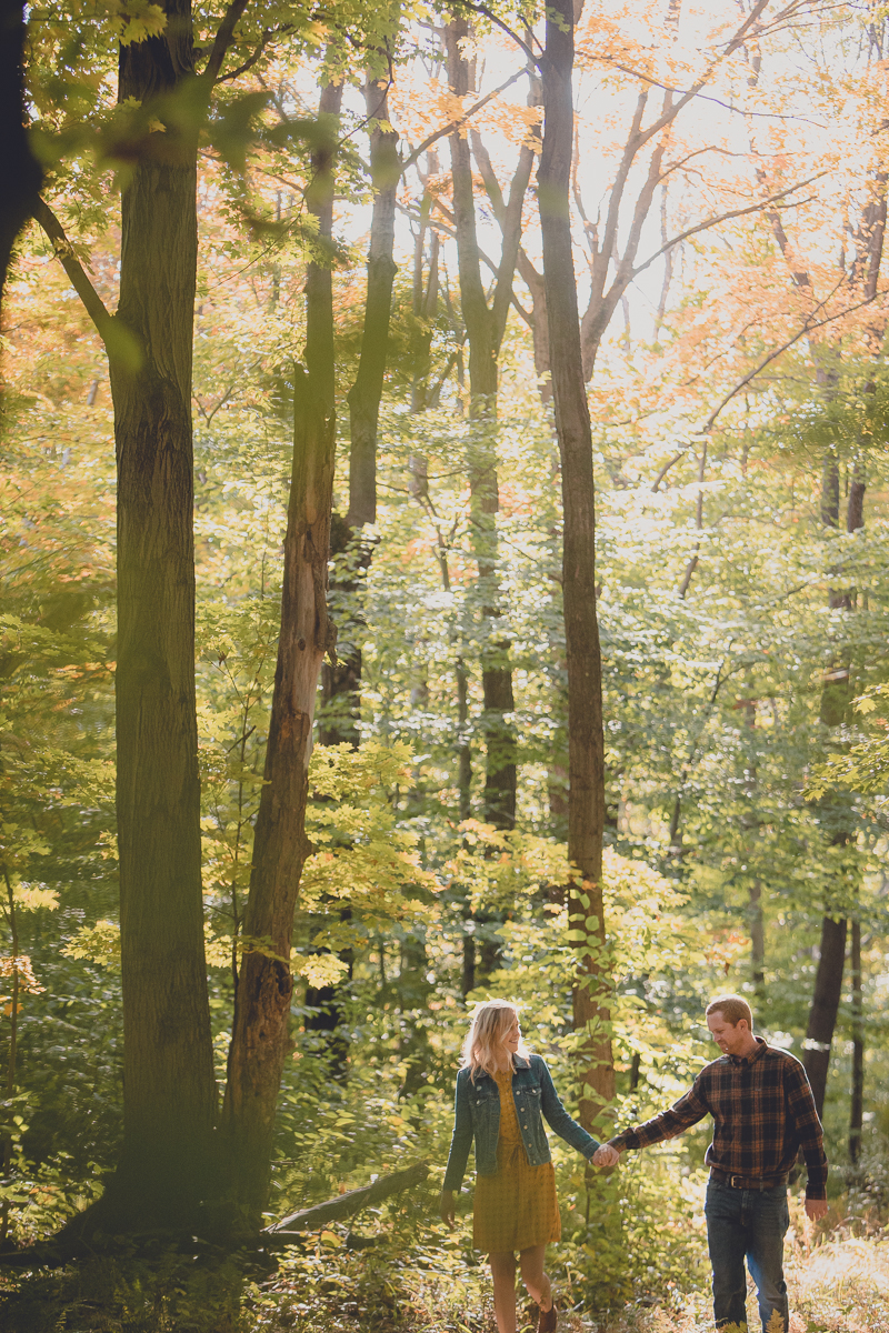 engaged couple holds hands and walks in woods during engagement photography session near Ellicottville, NY