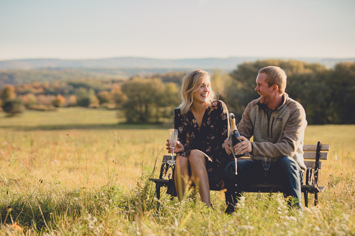 bride and groom cheers champagne on bench in field during their wedding engagement portrait photography session in Ellicottville, NY