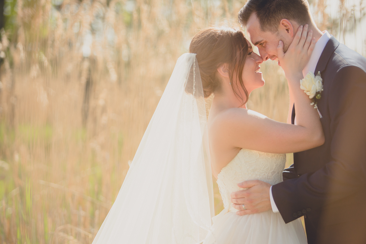 bride and groom touch noses on wedding day in field at Tifft Nature Preserve in Buffalo, NY