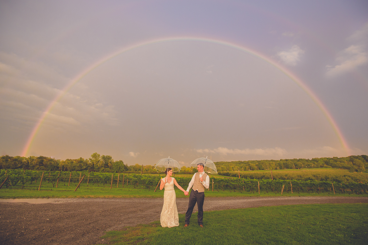 bride and groom hold hands under clear umbrellas beneath rainbow during their wedding reception at freedom run winery in WNY
