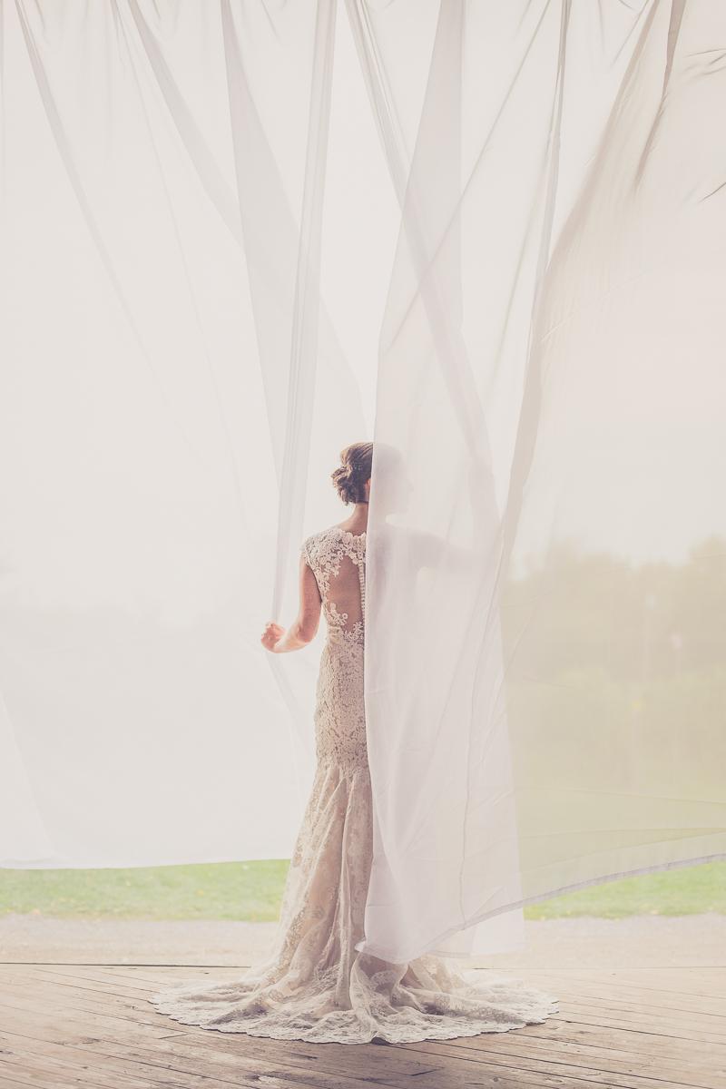 brides stands in drapes of doorway to barn at Freedom Run Winery wedding venue in Niagara County, near Buffalo, NY