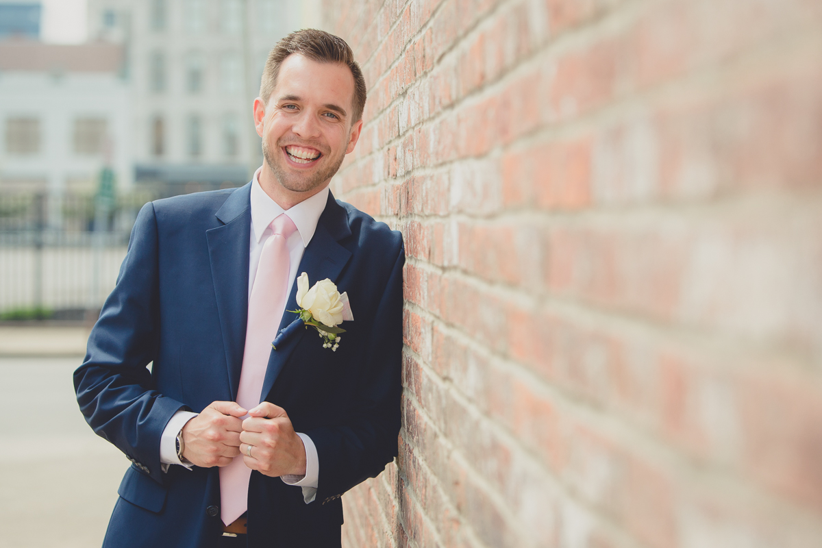 groom leans on brick wall and smiles for photographer on wedding day next to Greetings from Buffalo Mural in Buffalo, NY