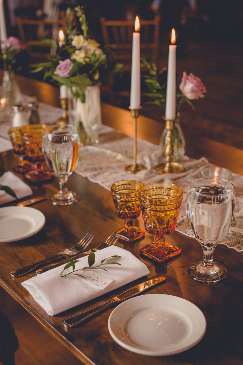 vintage place settings from Quaint Rentals with brass candles and whimsical flowers and greenery sit on lace table runner of rustic table at wedding at Pearl St. Grill and Brewery in Buffalo, NY