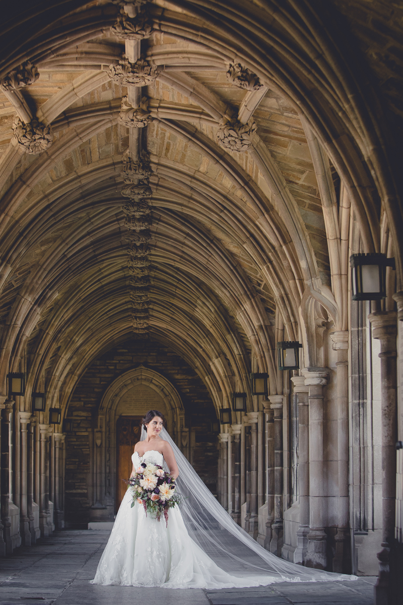 bride stands for wedding portrait in archway by Sage Chapel on the Cornell University campus in Ithaca, NY