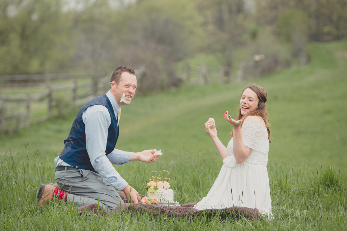 bride and groom enjoy wedding cake in field at Knox Farm State Park during their small, intimate wedding elopement celebration