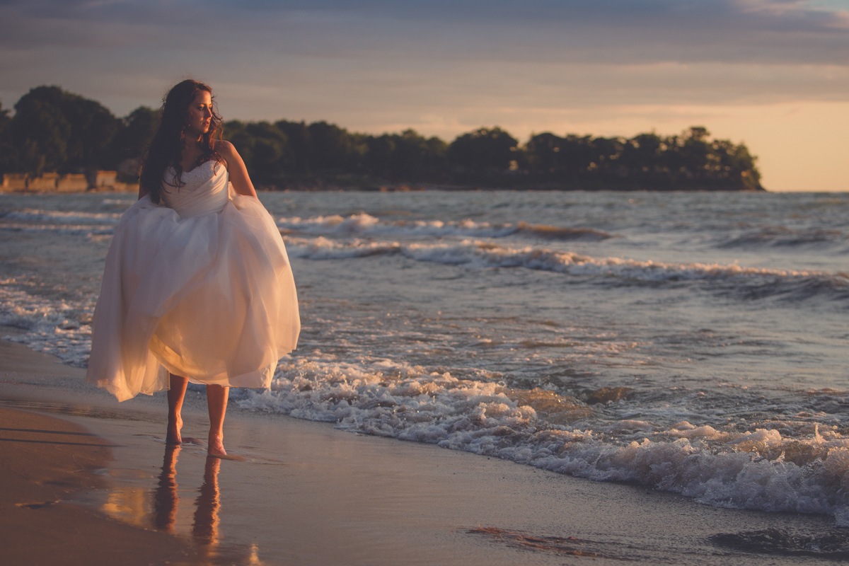 wedding photography of bride walking down beach at Camp Pioneer on Lake Erie at sunset
