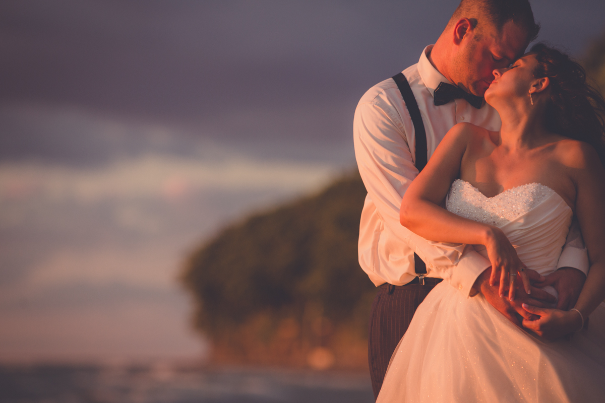 wedding photography of bride and groom embracing on beach at Camp Pioneer on Lake Erie at sunset