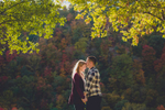couple stands in Niagara River Gorge in front of fall folliage during wedding engagement portrait photography session at Artpark in Lewiston, NY
