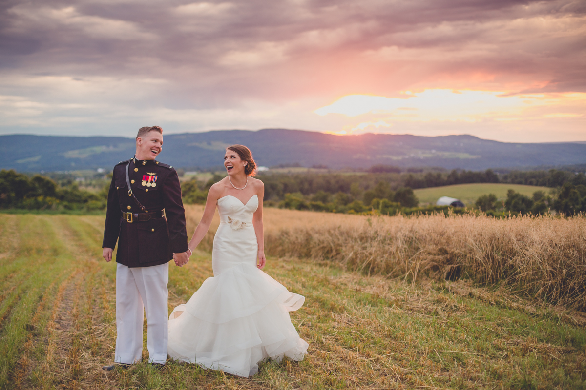 bride and groom hold hands and look at each other on mountain top at sunset in the Adirondacks of NY