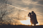 couple looks at each other in silhouette during sunset at buffalo harbor state park during wedding engagement photography session