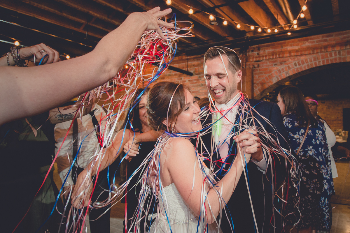 bride and grooms family throws ribbons on them during first dance at their pearl st grill and brewery wedding