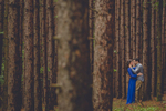 engaged couple hugs in pine forest during their engagement portrait photography session in buffalo, NY