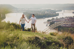couple holds hands near incline rail in grass overlooking rivers and bridges in Pittsburgh, PA during their engagement photography portrait session
