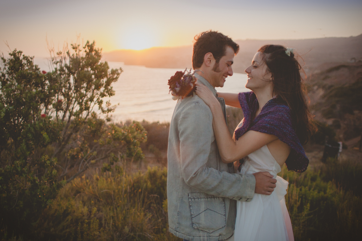 Bride and groom laughing on cliff at Rachos Palos Verdes Beach in California on their wedding day