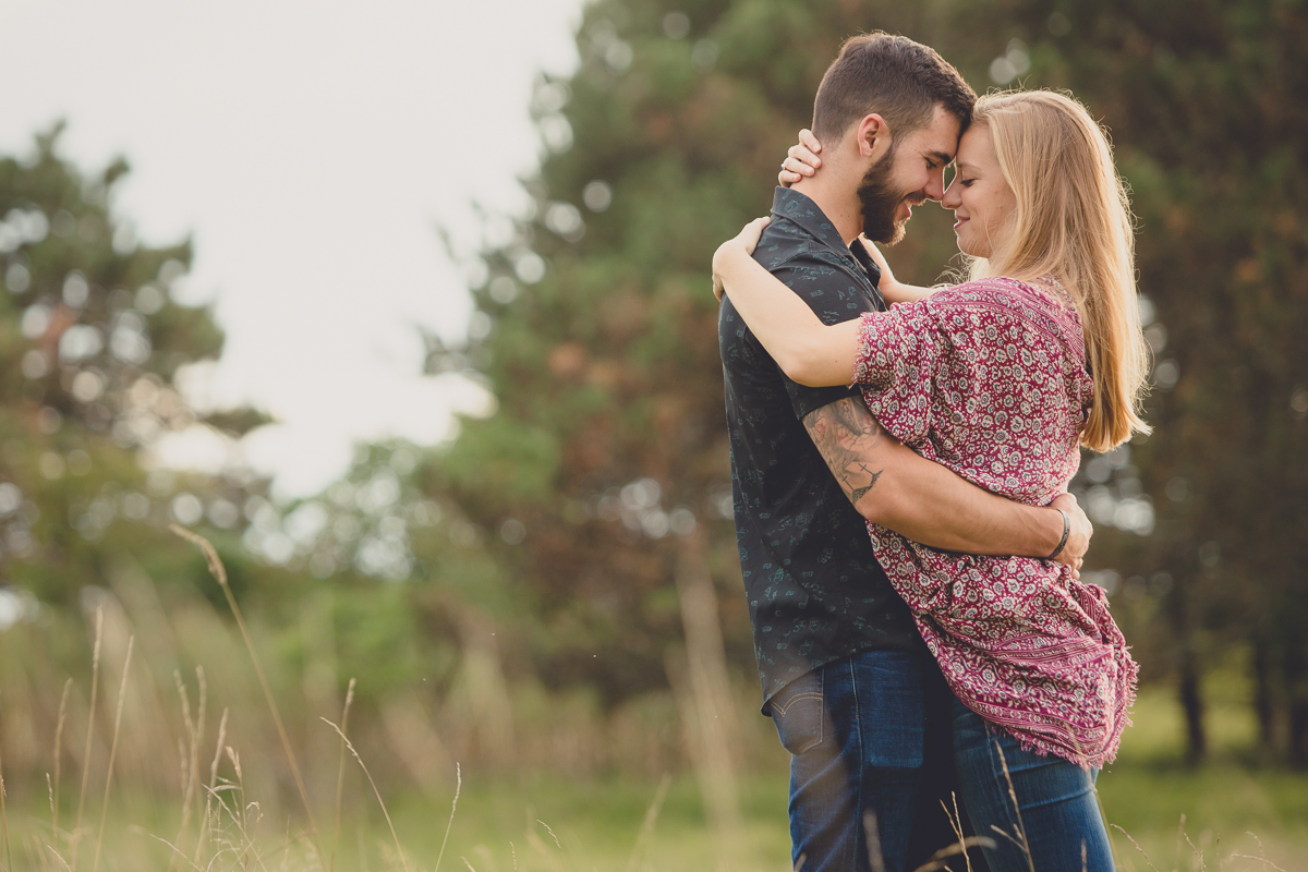 couple touch foreheads while hugging during their wedding engagement photography session in field at Tifft Nature Preserve in Buffalo NY