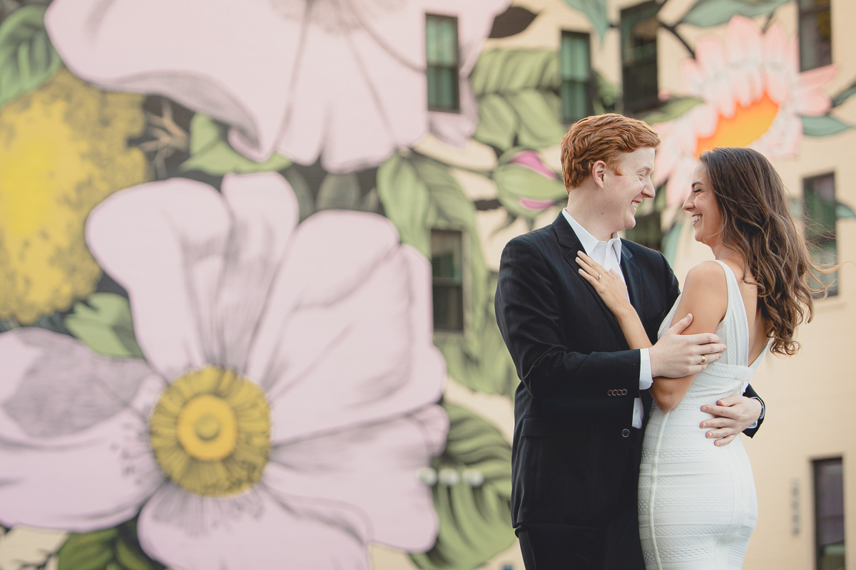 bride and groom laugh while embracing in front of the {quote}wildflowers for Buffalo{quote} mural in downtown Buffalo, NY during their wedding engagement portrait photography session