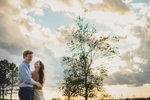 bride and groom laugh during sunset in field at Tifft Nature Preserve in Buffalo, NY during their wedding engagement photography session