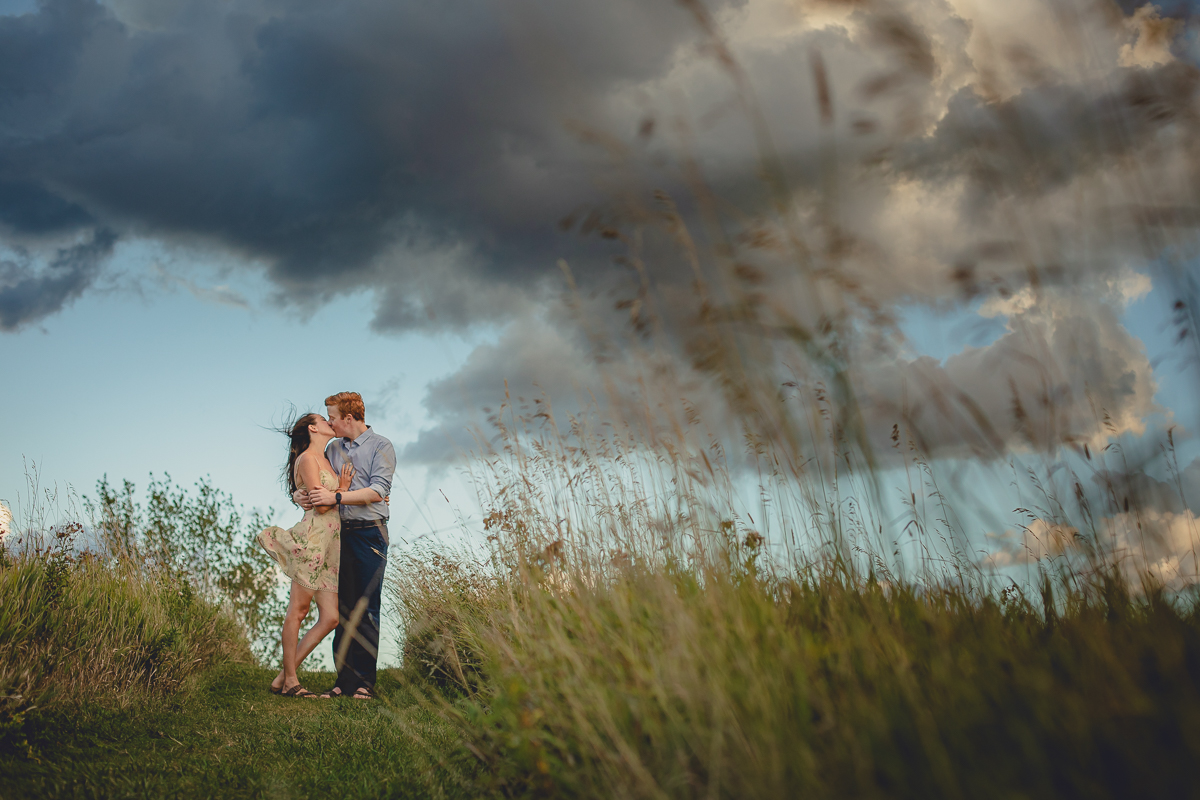 bride and groom kiss during sunset in field at Tifft Nature Preserve in Buffalo, NY during their wedding engagement photography session