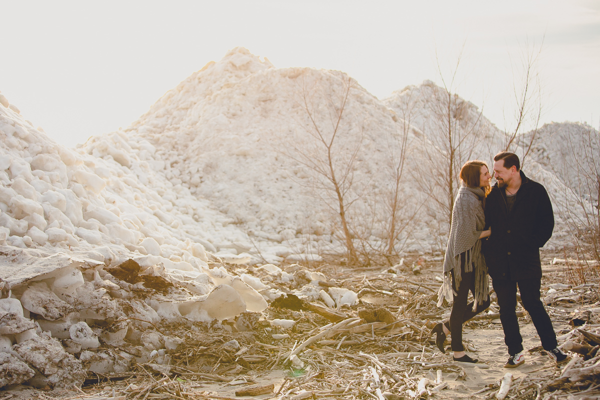 couple look at each other while smiling in front of ice during woodlawn beach winter photography session near Buffalo, NY