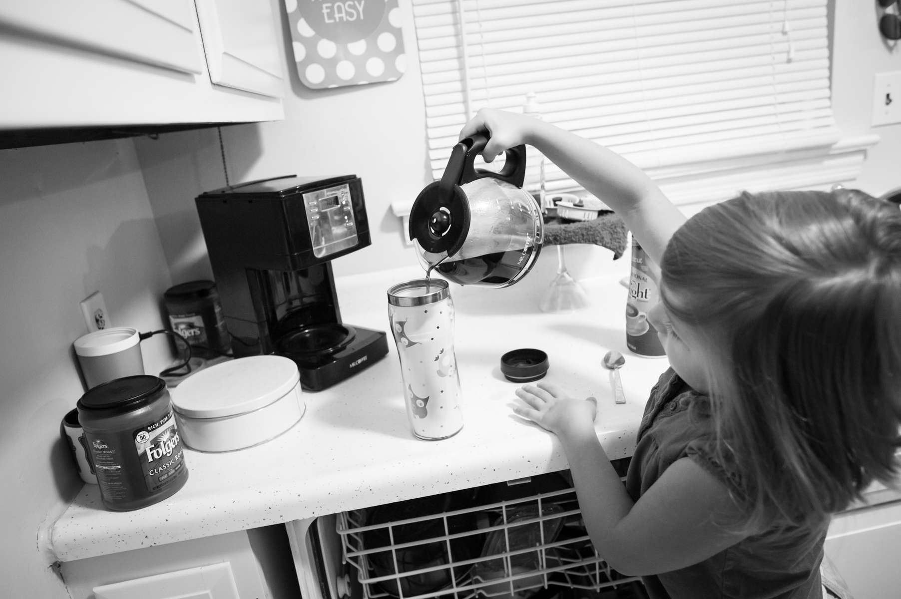 Zoey McCarver, 8-years-old, prepares a traveling mug of coffee for her mom, Caitlin Bell, before they leave for school and work on August 21, 2013 in Chattanooga, TN.