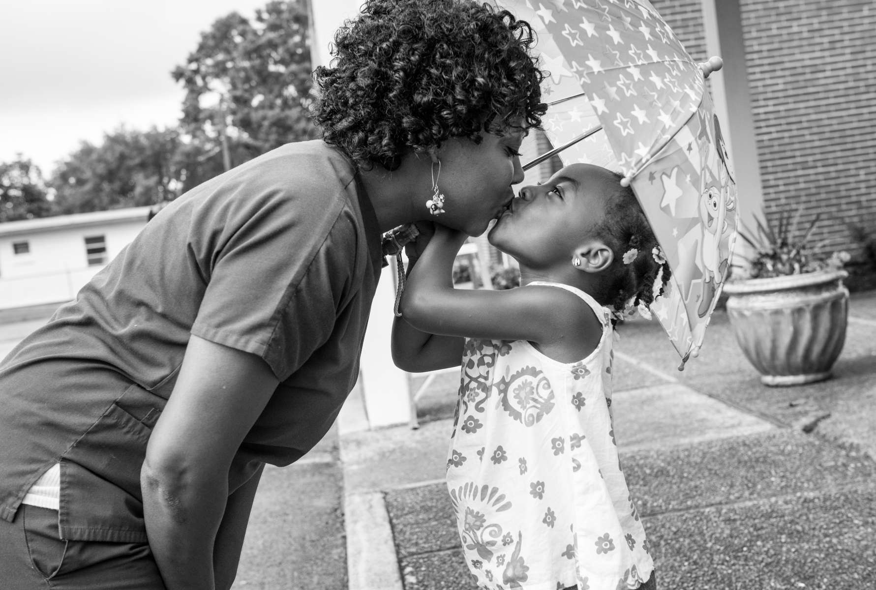 Nikki Brown and her daughter Kristian, 4-years-old, share a moment under an umbrella outside church in Chattanooga, TN on August 21, 2013.