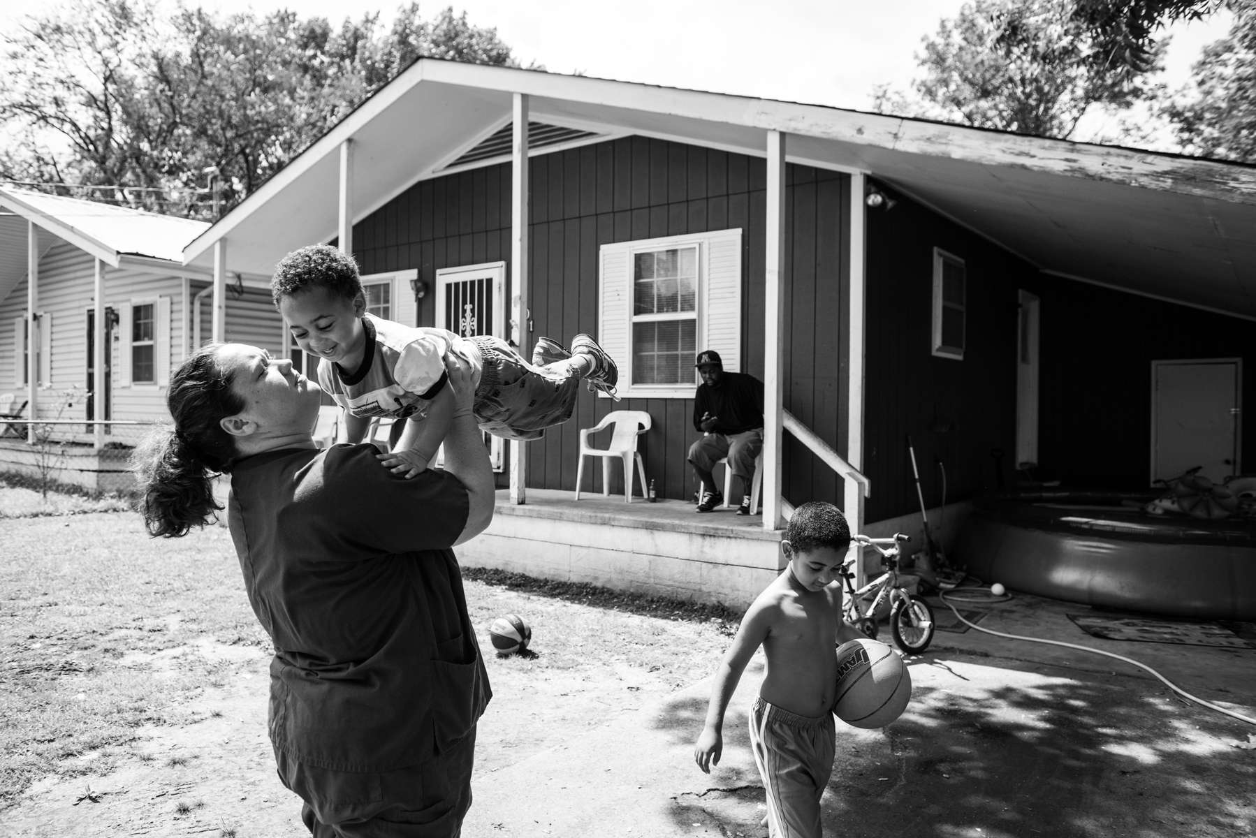 Jessica McGowan with sons Keylan, age 2, and Jacob, age 5, in front of the house she currently shares with her mother. Jessica is moving to another house in a subsidized housing project, to move back in with her children's father (pictured on the porch.)