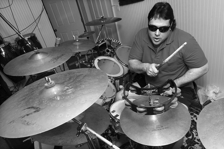 Marcus Padula, drummer for Deep Blue dJinn, lost his sight in an industrial accident when he was in his 20's. After the accident, Padula took up the drums. Today, Padula performs with the band in the Metrowest Boston area.