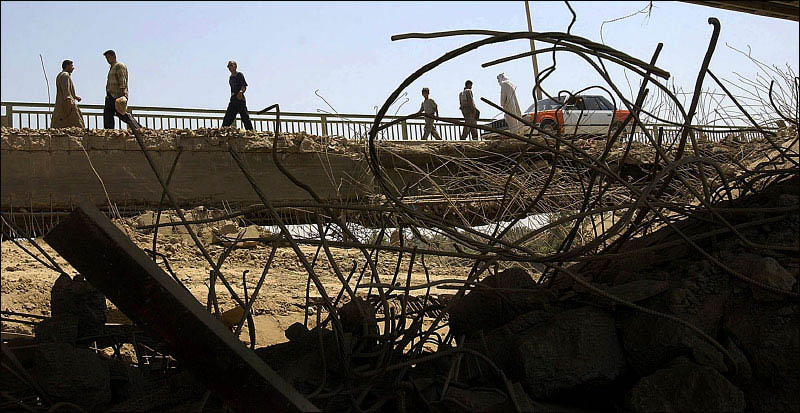 Iraqis are framed by the wreckage of the Dyalaa Bridge south of Baghdad as they walk across a temporary span.