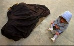 A mother lies covered under a black cloth shaking with sickness as her three-year-old daughter plays with a cup.