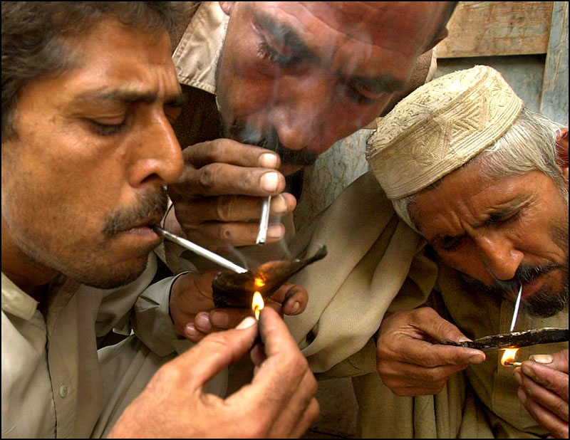 Three men huddle in a corner to smoke heroin away from the crowds and vendors of the Old Bazaar in Peshawar. Inhaling the smoke is known as {quote}chasing the dragon.{quote} In the city of 300,000 there are 40,000 heroin users with Afghanistan supplying the drug.