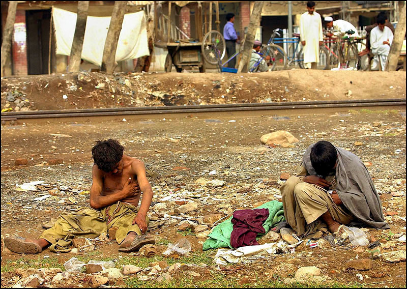 The side of the road is home for two heroin addicts outside the bazaar area in Peshawar.