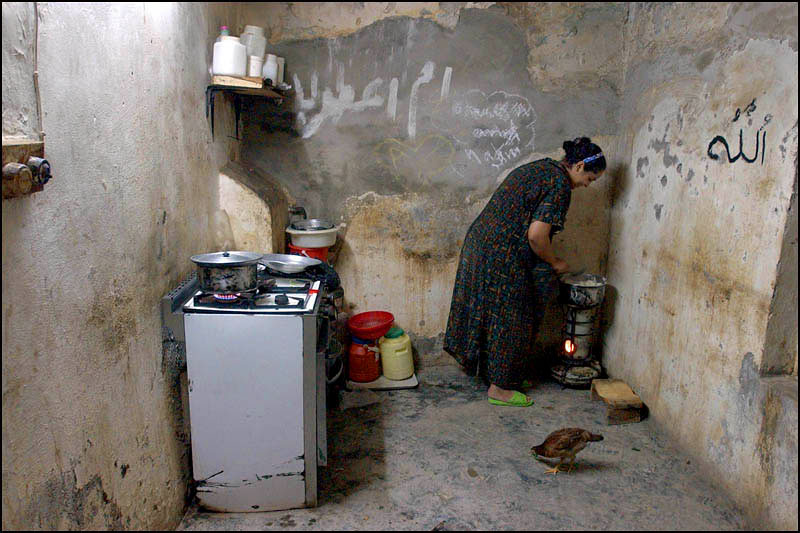 Nakam Amar, 23, cooks lunch in the kitchen of her home in the Al-Hurya section of Baghdad. Water must be boiled everyday to clear it of bacteria.