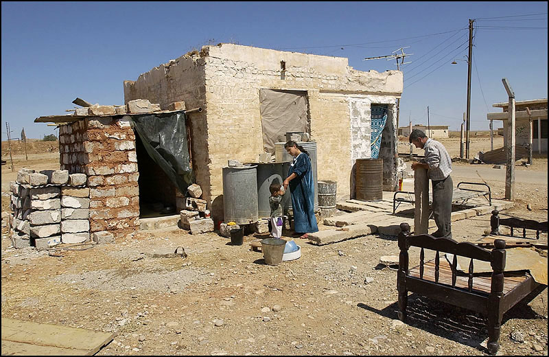 Kamal gives their two-year-old son, Mohammad Yuns, a drink from a plastic container while her husband, Yuns Abdullah Mohammed, works on their home.