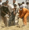 Bodily remains are removed from a mass grave discovered at a Iraqi intelligence base 30 miles south of Baghdad.