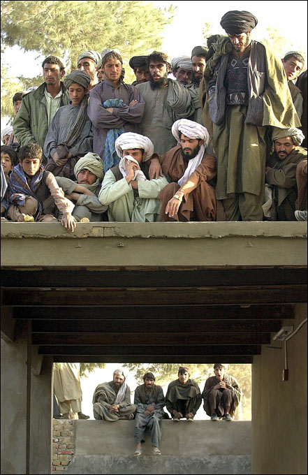 Afghans from Spin Boldak gather on a wall surrounding a compound where Tayyeb Agha, secretary and spokesman for Taliban supreme leader Mullah Mohammed Omar, holds a news conference.