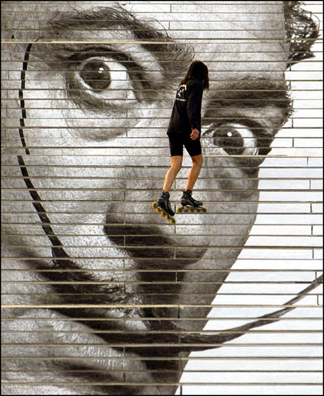A rollerblader wheels across a photo-billboard of Salvador Dali at the Philadelphia Museum of Art.