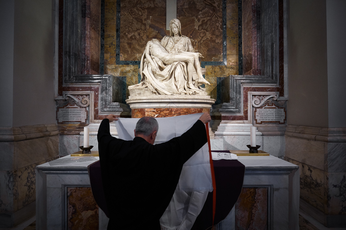 Michelangelo's La Pietà stands over preparations for a mass led by Pope Francis in St. Peter's Basilica.