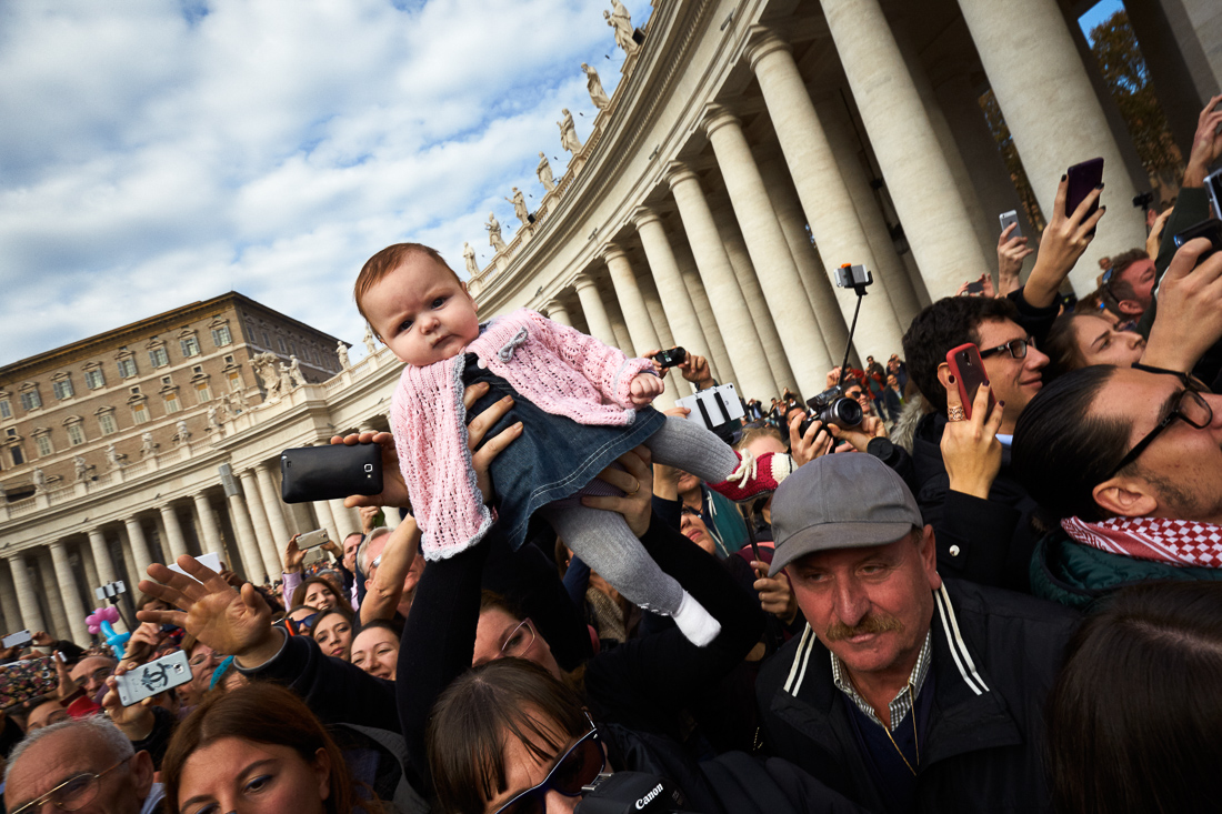 Children are offered up by their parents to Pope Francis for blessing at a general audience in Vatican City.