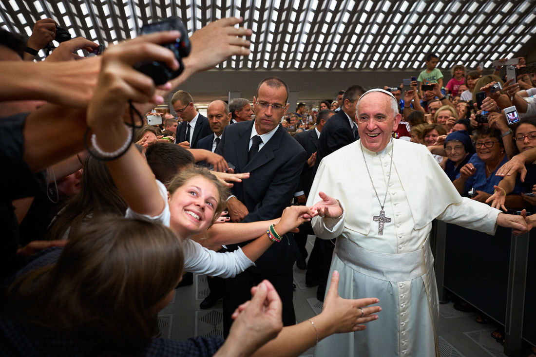 An enthusiastic pilgrim takes a selfie photo with Pope Francis during a general audience in Vatican City.