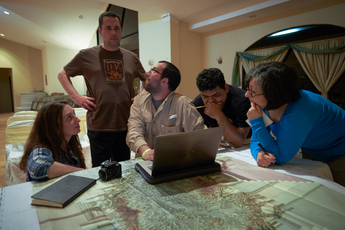 Team specialists Anna Cohen, in plaid shirt, Chris Fisher in IPA t-shirt, Juan Carlos Fernandez Diaz in kaki shirt,, Oscar Neil Cruz in black t-shirt, and Alicia Gonzalez in blue shirt, reviewing LiDAR images and maps before their foray into the jungle to search for a lost city in the Mosquitia in Honduras.From an airfield near Catacamas, Honduran soldiers, former British SAS commandos and scientists penetrated the Mosquitia jungle by helicopter to investigate structures left by an ancient culture that were neighbors to the Maya.