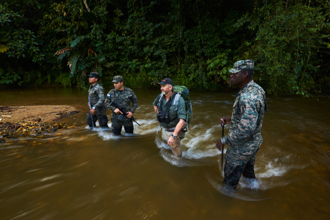 Andrew Wood, a former British SAS solder, now representing TAFFS (Television and Film Facilitation Services), center, stands with Honduran troops in a river while waiting for a team of scientists to catch up with them.