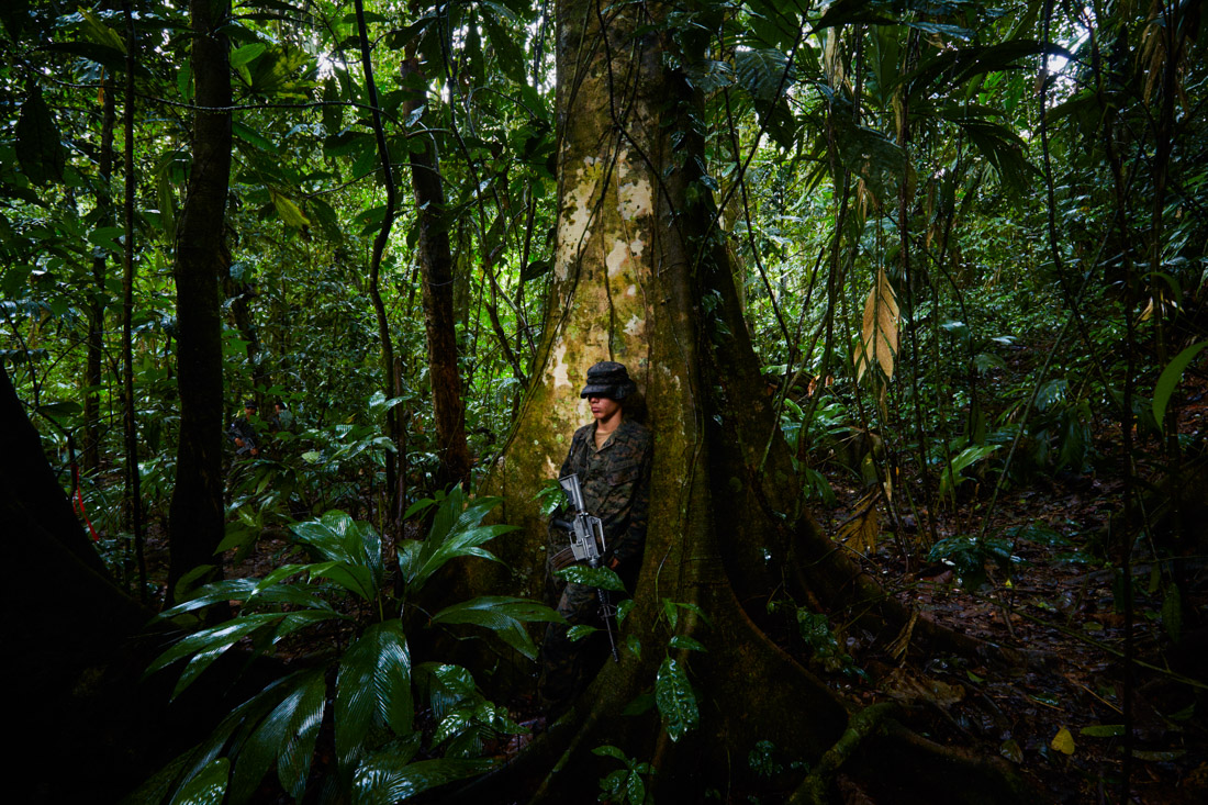 A Honduran soldier finds a refuge from rain in the jungle while providing protection to the group of specialists examining a cache of artefacts.