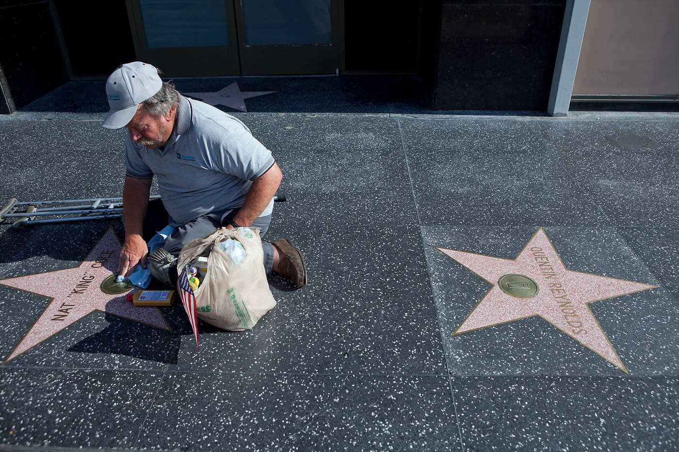 A one legged man polishes stars on Hollywood Boulevard, Line 302.
