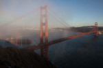 A ship heads out to sea as the evening fog rolls in around the Golden Gate Bridge.