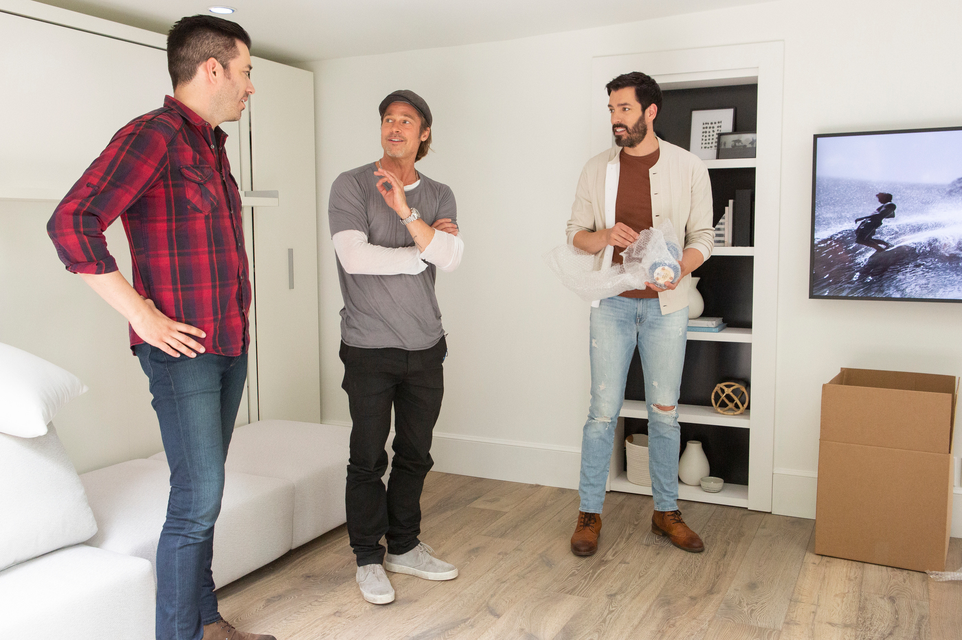 Brad Pitt and hosts Drew Scott (R) and Jonathan Scott (L) discuss the renovation of the garage of Jean Black, Brad Pitt's make-up artist and friend for 27 years. With the help of Brad Pitt, hosts Drew Scott and Jonathan Scott have transformed Jean's garage into a modern guest suite, in Santa Monica, California, as seen on Celebrity I.O.U.