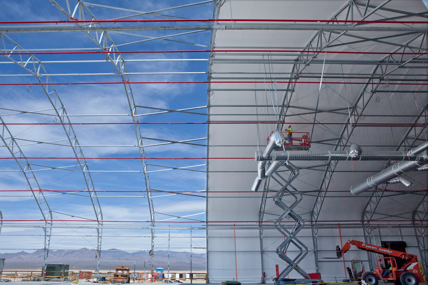 IVANPAH, CALIFORNIA, MAY 16 2011: A worker installs AC conduits in one of the three temporary tents warehouses where the mirrors will be assembled at the Ivanpah Solar Electric Generating Facility (photo Gilles Mingasson/Getty Images for Bechtel).