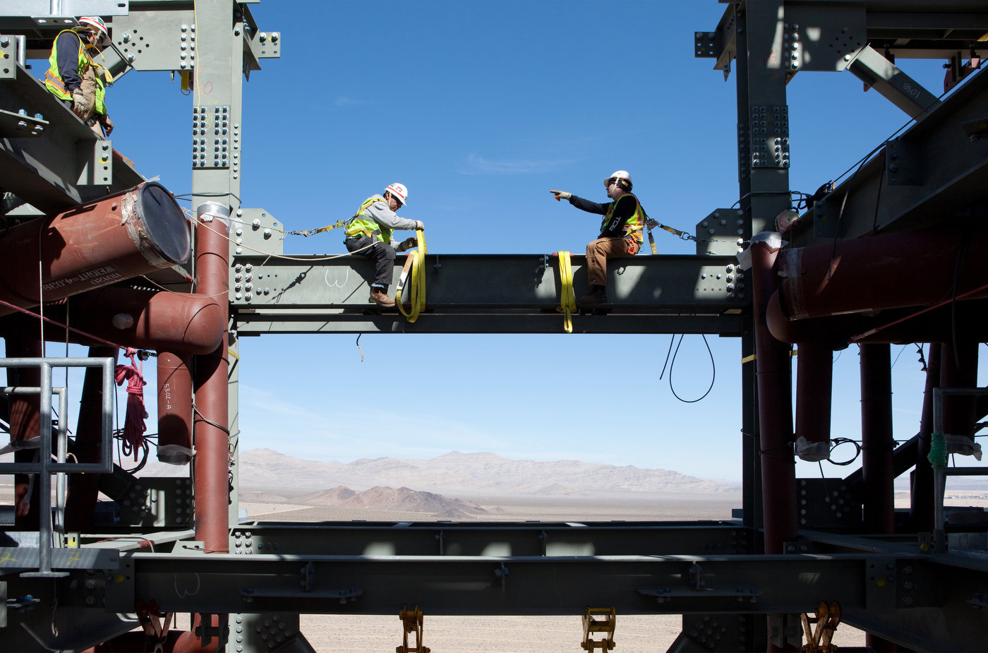 IVANPAH, CALIFORNIA, FEBRUARY 08 2012: Workers rig a steal beam on the top of Ivanpah's Tower One (photo Gilles Mingasson/Getty Images for Bechtel).
