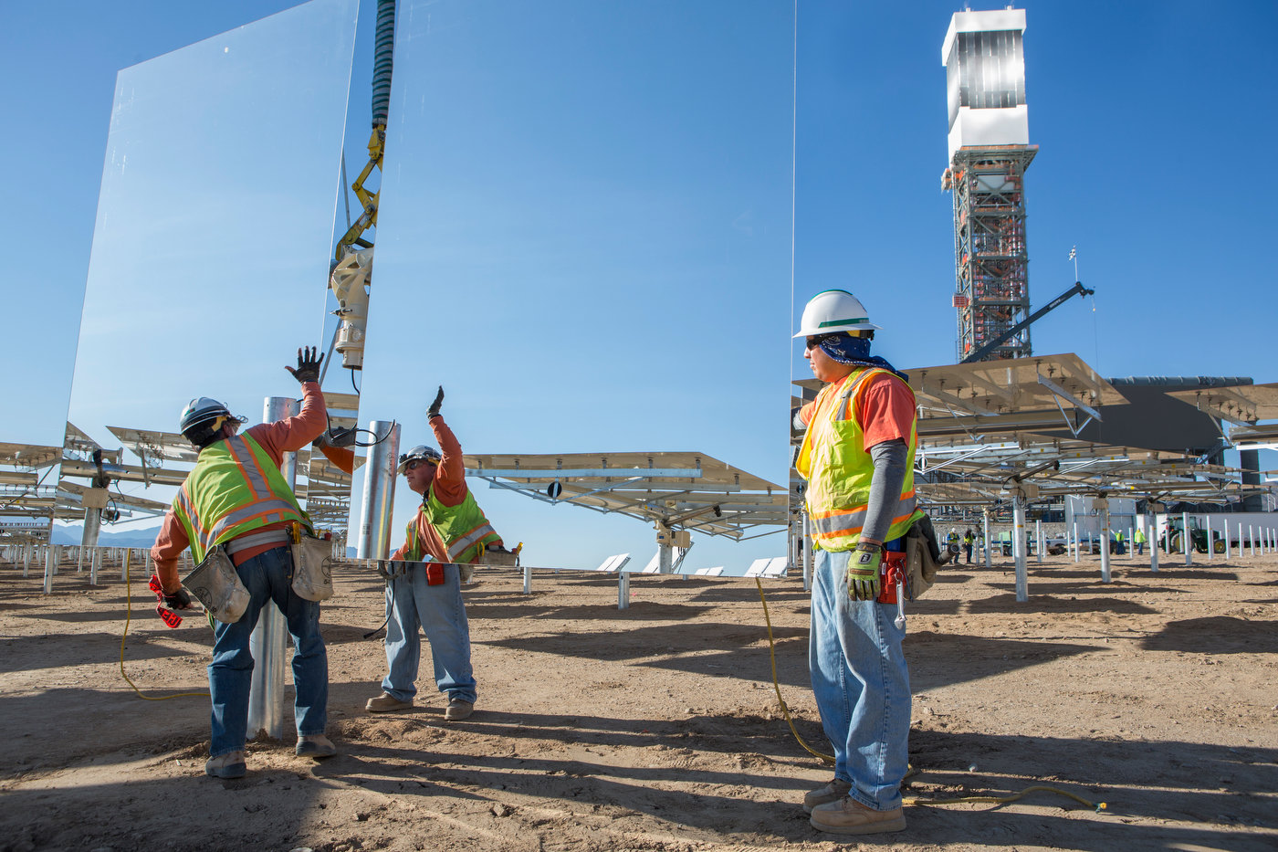 IVANPAH, CALIFORNIA, APRIL 03 2013: A crew secures a heliostat to its pylon near the base of Tower 1, which is {quote}lit{quote} during a steam blow test, at the Ivanpah Solar Power Facility. Located in the Mojave Desert 40 miles southwest of Las Vegas, The Ivanpah Solar Power Facility is a solar thermal power project, currently under construction, with a planned capacity of 392 megawatts, enough to power approximately 140,000 houses. It will deploy 170,000 heliostat mirrors spread over 4,000 hectares, focusing solar energy on boilers located atop three solar power towers, generating steam to drive specially adapted steam turbines The project, developed by Bechtel, will cost $2.2 billion and be the largest solar farm in the world (photo Gilles Mingasson/Getty Images for Bechtel).